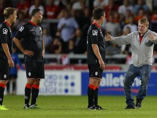 We're glad you're here. A fan greets Gary Neville and friends during a friendly at Salford City