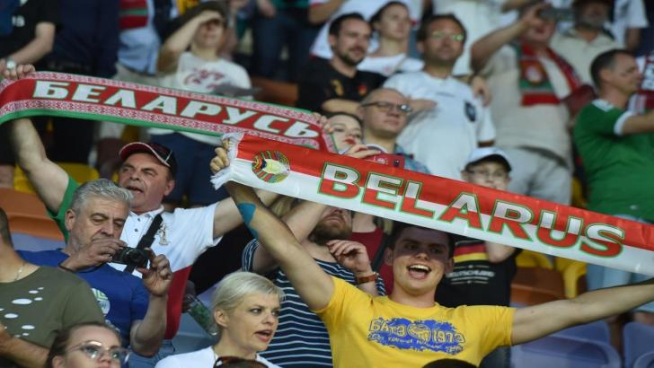 A football fan holds a Belarus scarf