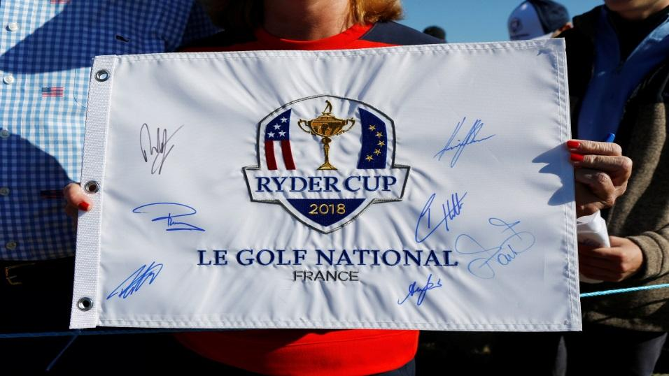 A fan holds an autographed Ryder Cup flag in Paris