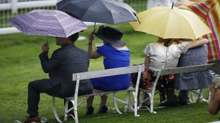 Racegoers shelter from the rain at Epsom