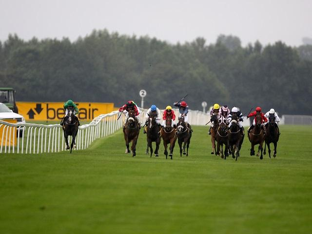 Victoria (centre, red silks, yellow helmet) riding at Ripon in August