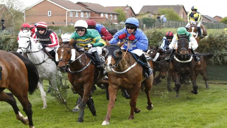 Raz De Maree (ridden by jockey in light blue) running in the Grand National at Aintree