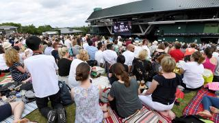 Tennis fans watch the action on the big screens at Wimbledon